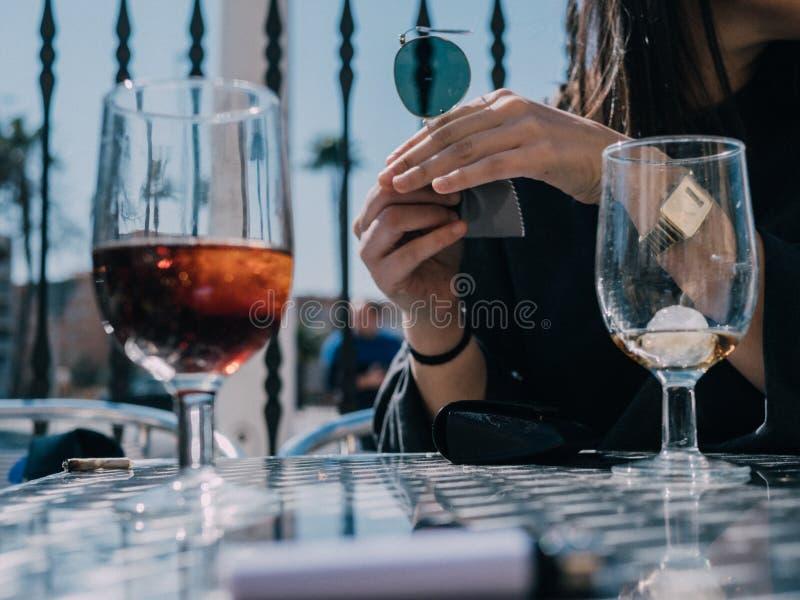 Unga och härliga vänner som har en uppfriskande drink på en terrass av en dagstång royaltyfria foton