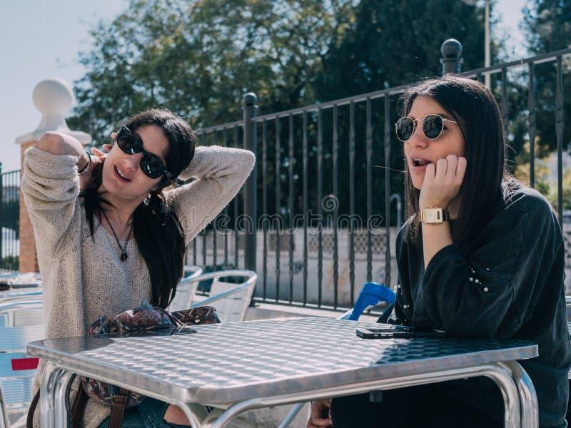 Unga och härliga vänner som har en uppfriskande drink på en terrass av en dagstång royaltyfri bild