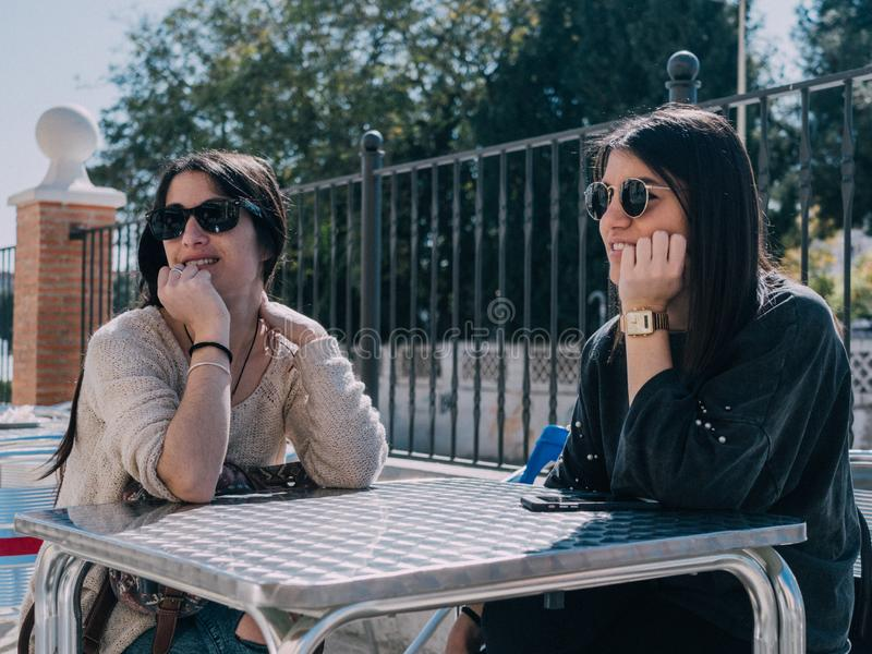 Unga och härliga vänner som har en uppfriskande drink på en terrass av en dagstång royaltyfri fotografi