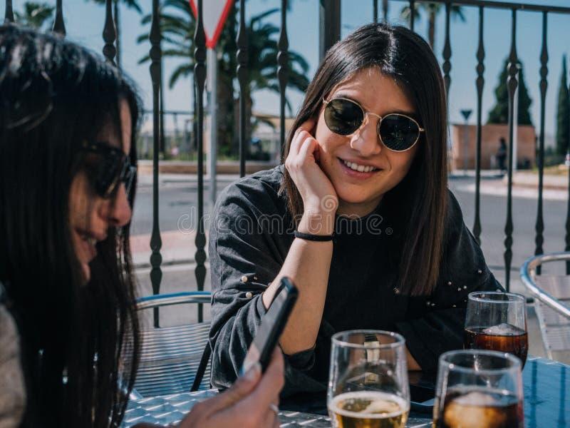Unga och härliga vänner som har en uppfriskande drink på en terrass av en dagstång arkivfoton