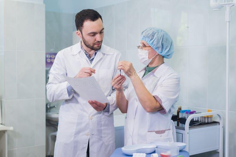 Unga och höga kemister som tillsammans arbetar och ser en provrör i ett kliniskt laboratorium arkivfoto