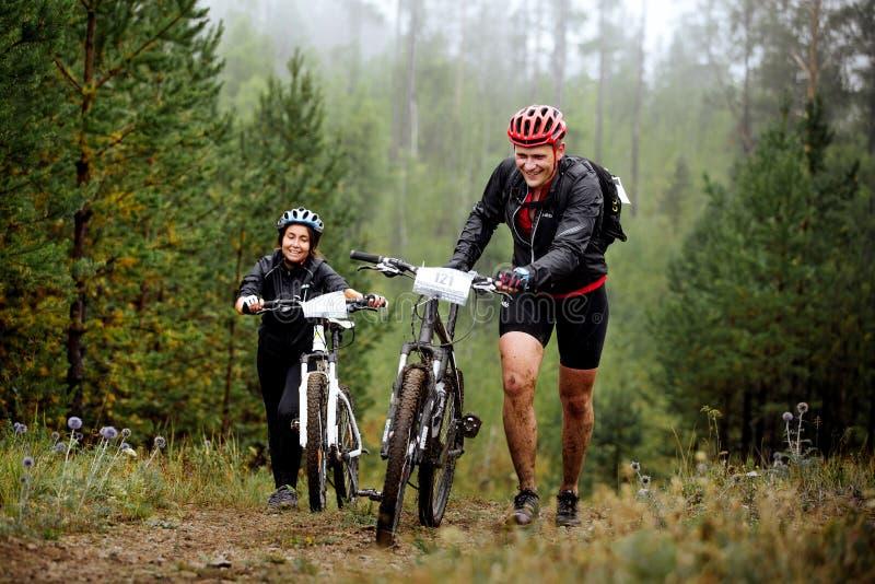 Unga par av cyklister går stigande med din mountainbike fotografering för bildbyråer