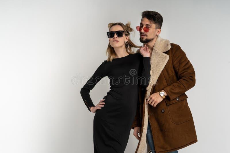 Unga par av den skäggiga mannen i lag och nätt kvinna i svart klänning med långt blont hår fotografering för bildbyråer