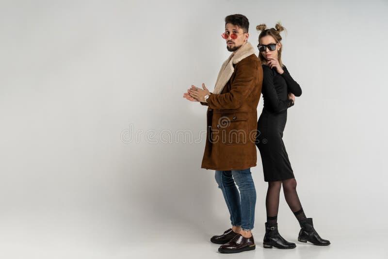 Unga par av den skäggiga mannen i lag och nätt kvinna i svart klänning med långt blont hår royaltyfri bild