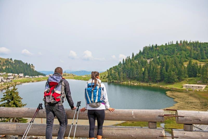 Unga par av fotvandrare nära sjön i berg royaltyfri fotografi