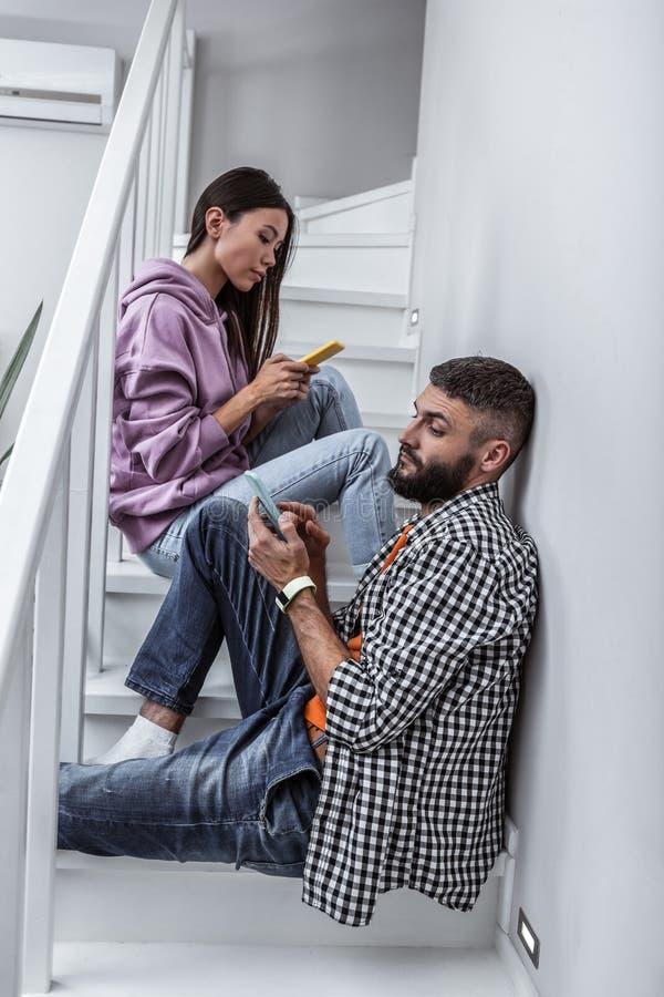 Unga par av freelancers som hemma som arbetar använder deras telefoner arkivfoton