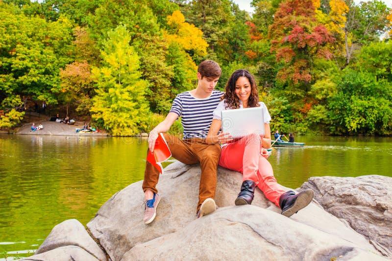 Unga par av mannen och kvinnan som utanför studerar royaltyfri fotografi