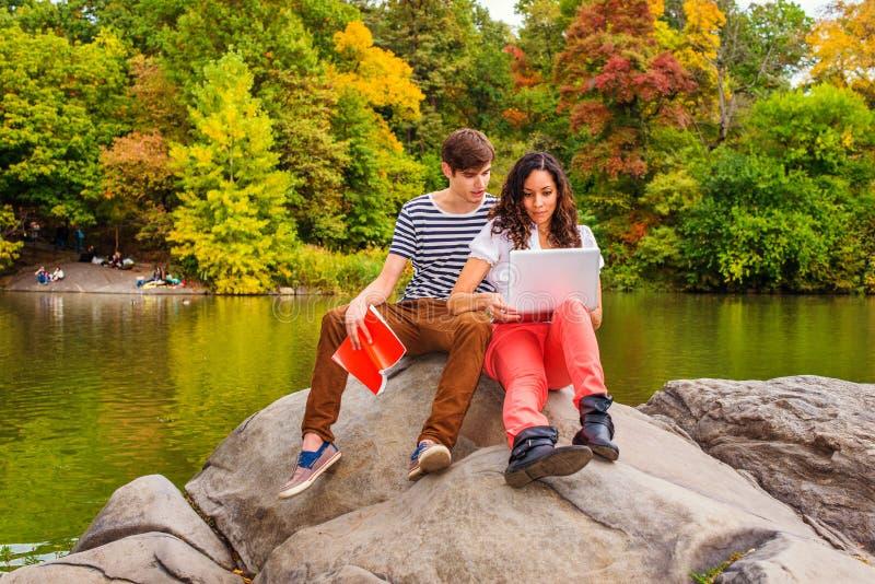 Unga par av mannen och kvinnan som utanför studerar royaltyfri foto