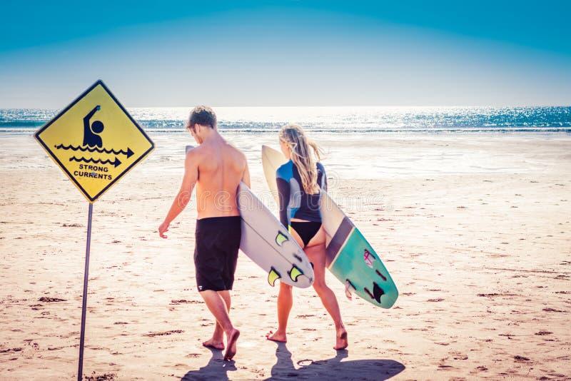 Unga par av surfare som går med där surfingbrädor i väg från fotografen in mot havet förbi starka strömmar arkivbild