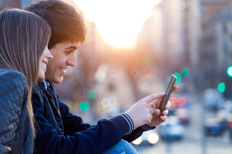 Unga par av turisten i stad genom att använda mobiltelefonen royaltyfria foton