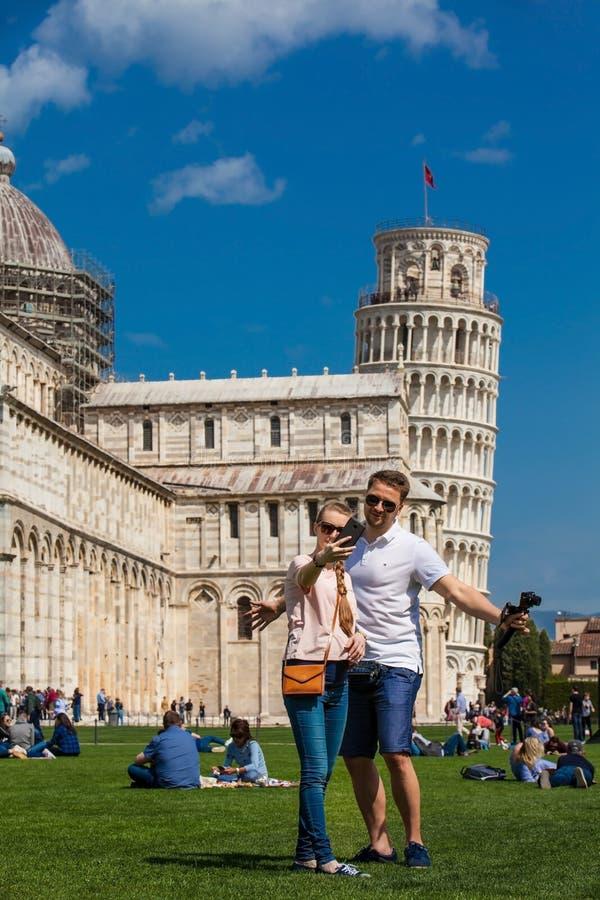 Unga par av turister som framme tar en selfie av det berömda lutande tornet av Pisa arkivbilder