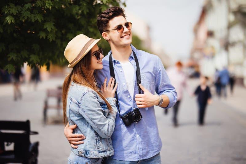 Unga par av turister som tar en gå i en stadsgatatrottoar i en solig dag arkivbilder
