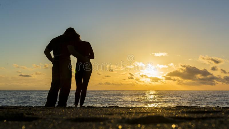 Unga par av vänner som rymmer händer in mot havet på solnedgången Förälskade man och kvinna royaltyfria foton