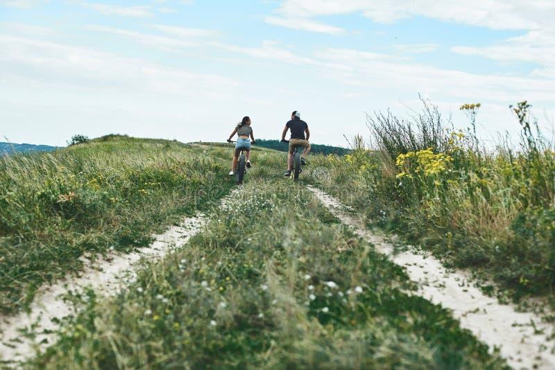 Unga par cyklar på fatbikes isolated rear view white arkivbilder