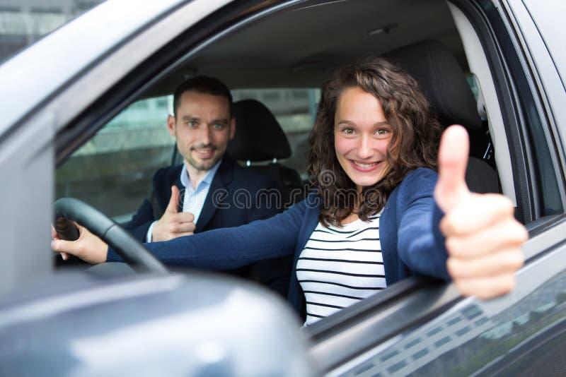 Unga par för affärsman i deras splitterny bil arkivbild