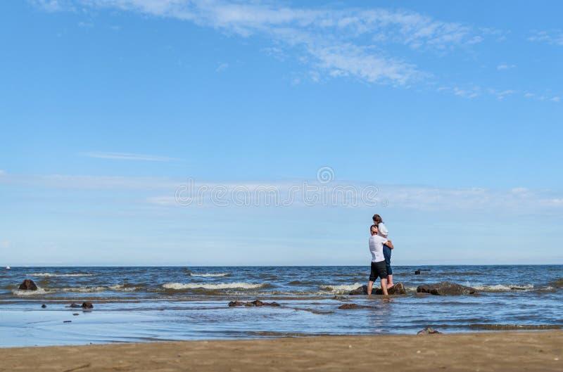 Unga par för romantiska vänner som tillsammans kopplar av på den tropiska stranden Man som kramar med kvinnan och att tycka om li royaltyfria bilder