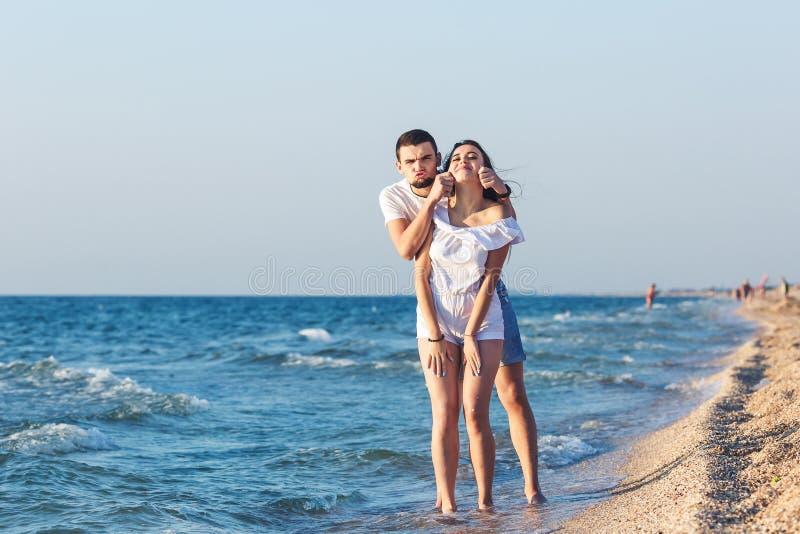 Unga par gör en framsida och att ha gyckel på stranden royaltyfri fotografi