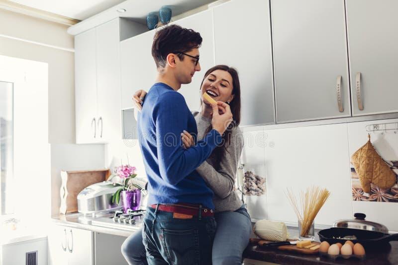 Unga par i k?ket som kramar och ?ter ost royaltyfria foton