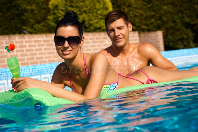 Unga par i simbassäng royaltyfria bilder
