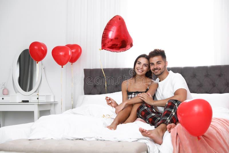 Unga par i sovrum med luftballonger Ber?m av den Sanka dagen f?r valentin` s arkivfoto