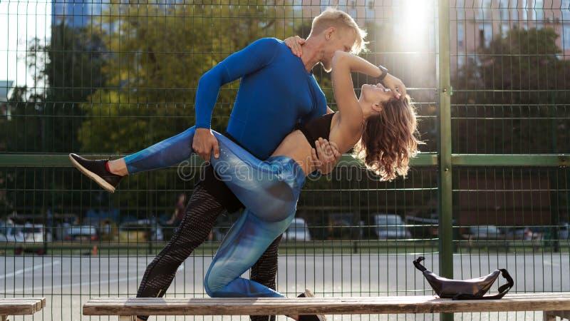Unga par i sportwear, når de har joggat ha, vilar royaltyfri bild