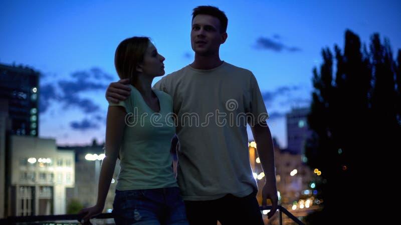 Unga par i tillfällig kläder som meddelar, efter-arbete går i aftonstad royaltyfria foton