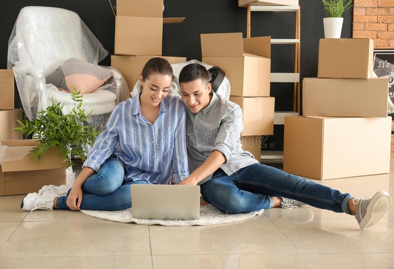 Unga par med bärbara datorn som inomhus sitter på golv nära askar flytta sig f?r hus som ?r nytt arkivbild