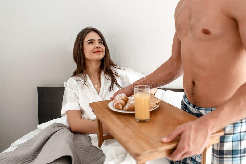 Unga par med den romantiska frukosten i sängen Den lyckliga härliga kvinnan ser lyckligtvis på hennes älskling arkivfoton