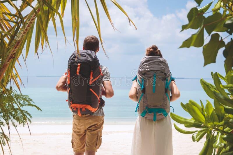 Unga par med den stora ryggsäcken som går till stranden i en tropisk feriedestination arkivbild