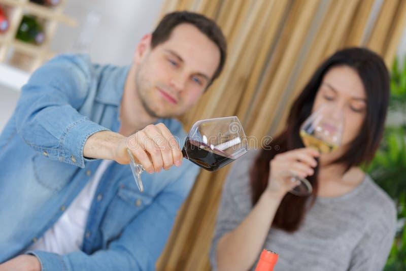 Unga par med exponeringsglasvin i restaurang arkivbild
