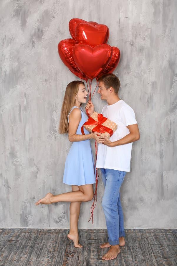 Unga par med hjärta formade röda ballonger och gåvaasken nära den gråa väggen inomhus royaltyfria bilder