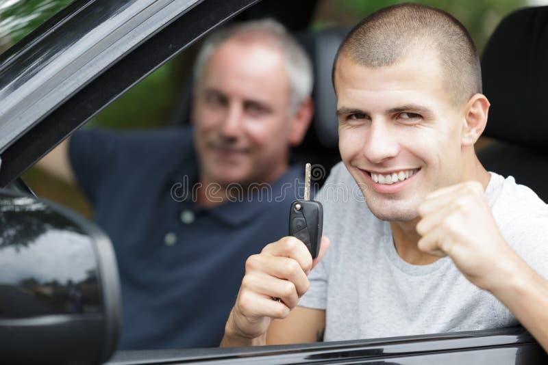 Unga par med nycklar till nya bilar royaltyfria foton