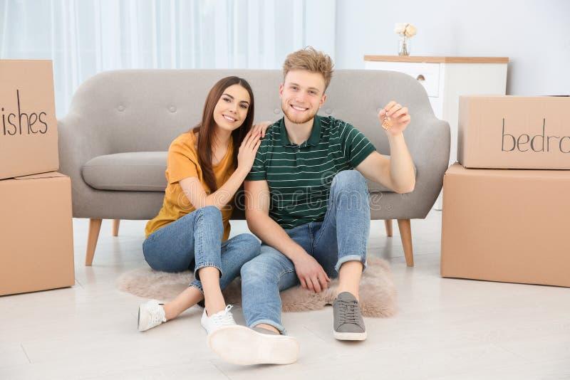 Unga par med tangent från deras nya hus inomhus royaltyfria foton