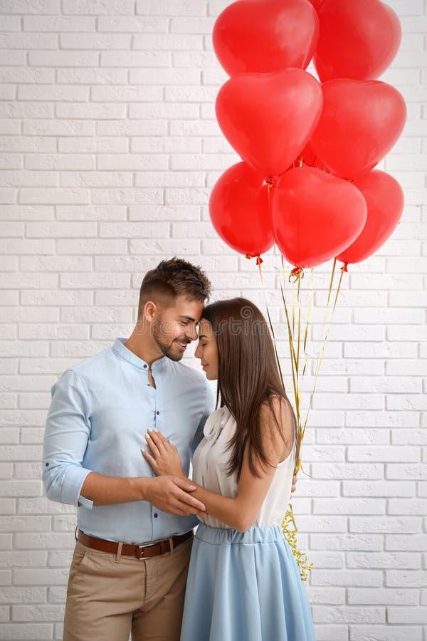 Unga par med väggen för tegelsten för luftballonger den vita Ber?m av den Sanka dagen f?r valentin` s royaltyfri bild