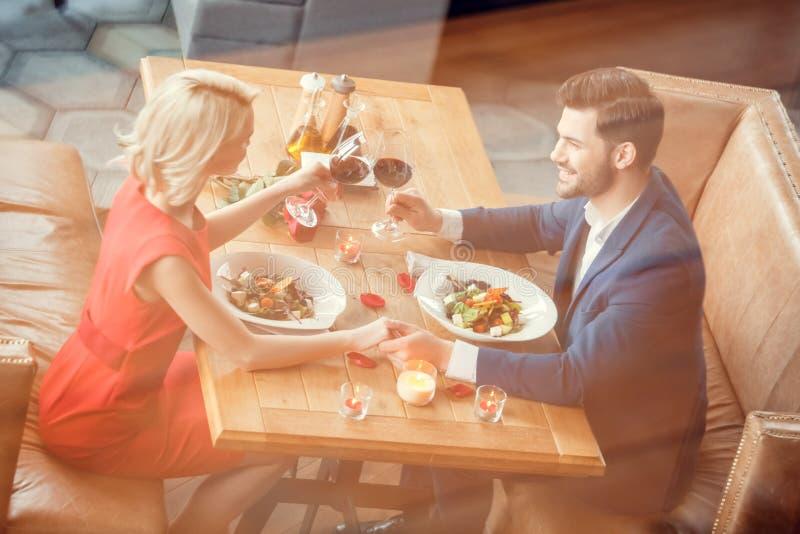 Unga par på datum i restaurangen som sitter äta sallad som rymmer jubel för vinexponeringsglas som rymmer gladlynt bästa sikt för fotografering för bildbyråer