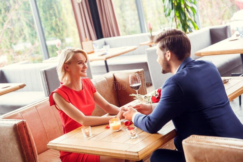 Unga par på datum i restaurangen som sitter rymma händer som ser de lyckliga arkivfoto