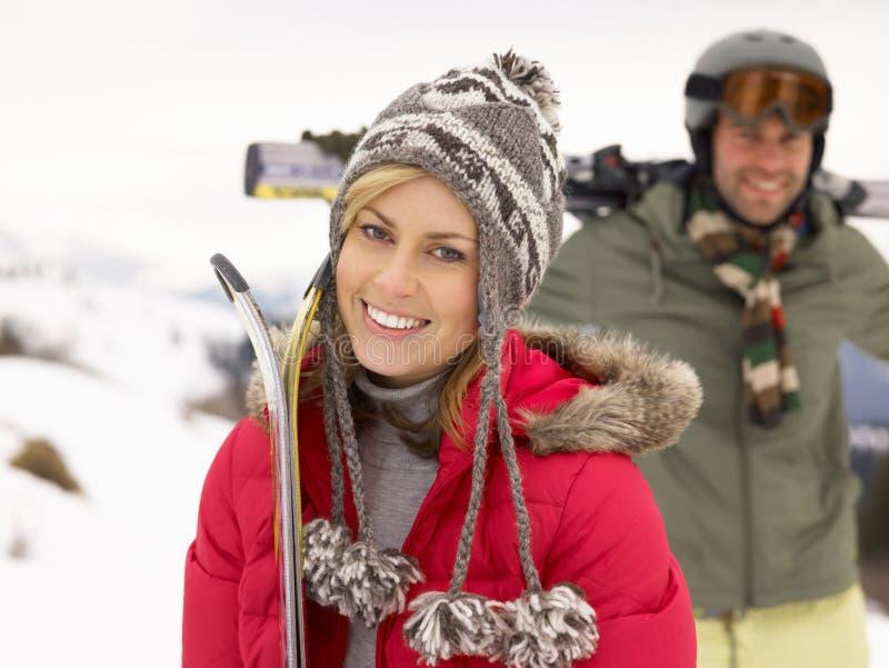 Unga par skidar på semester royaltyfri foto