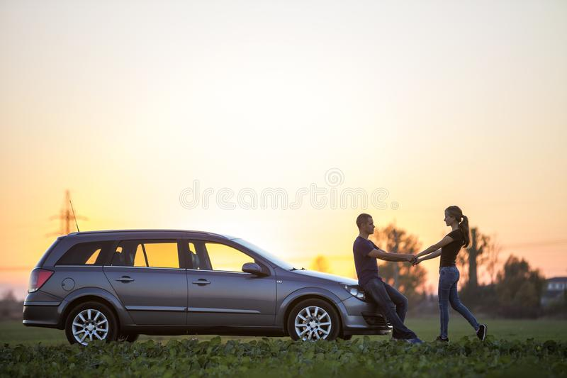 Unga par, slank attraktiv kvinna med den långa hästsvansen och stiligt mananseende på silverbilen i grönt fält på klar himmel på arkivbild