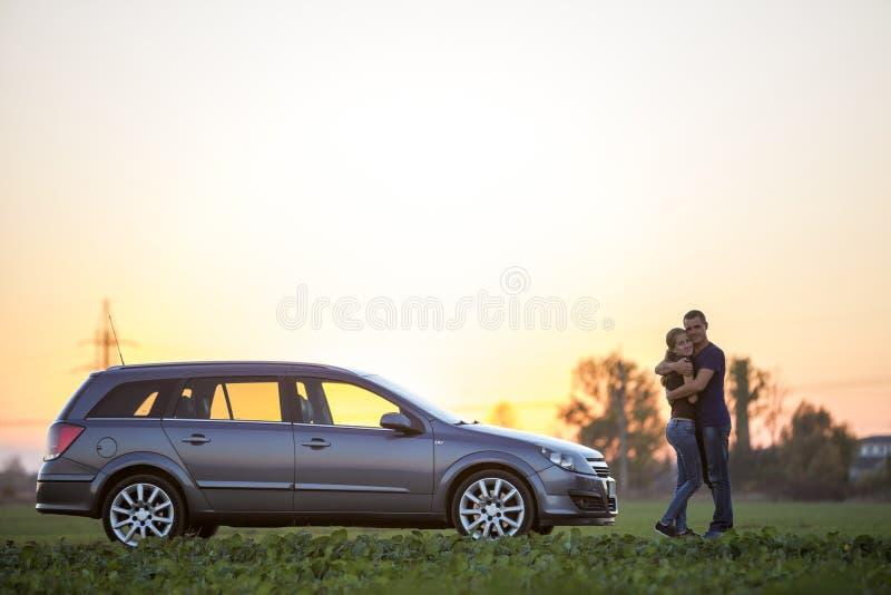 Unga par, slank attraktiv kvinna med den l?nga h?stsvansen och stiligt mananseende p? silverbilen i gr?nt f?lt p? klar himmel p? arkivfoton