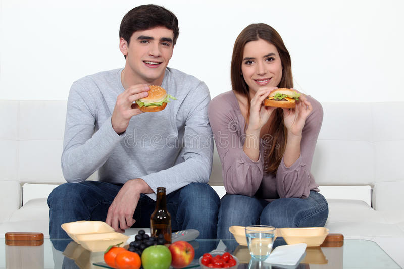 Unga par som äter hamburgare arkivbilder