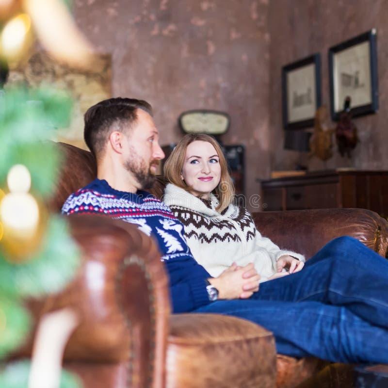 Unga par som bär varma ärmlös tröja, medan koppla av på soffan i vinden royaltyfri fotografi