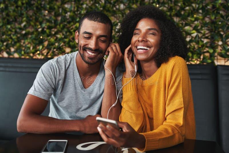 Unga par som delar hörluren för lyssnande musik på mobil phon royaltyfri bild
