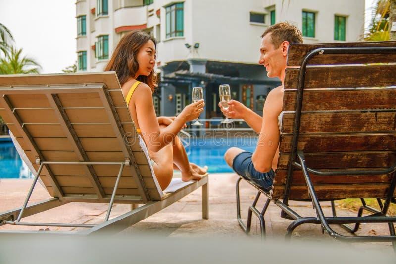 Unga par som firar och ligger på sunbeds, sommarsemestrar och drickachampagne royaltyfri bild