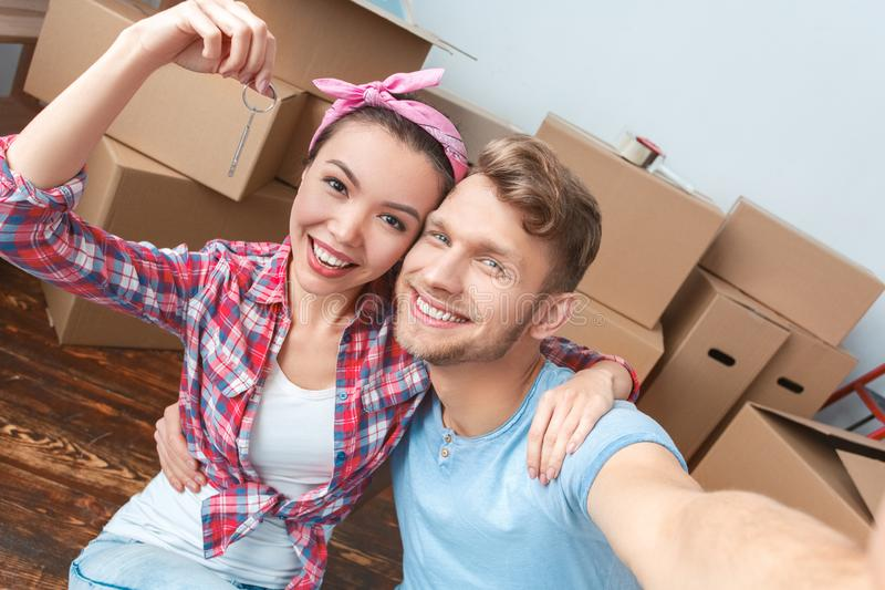 Unga par som flyttar sig till det nya ställeanseendet som tar selfiefoto på smartphonen som rymmer nyckel- glad närbild royaltyfri bild