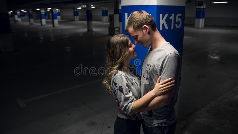 Unga par som går över det parkera garaget royaltyfri bild