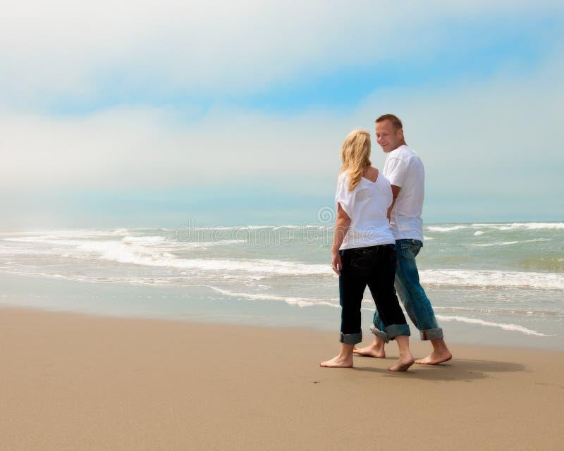 Unga par som går bort på stranden royaltyfria foton