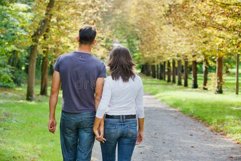 Unga par som går i höstpark royaltyfria bilder