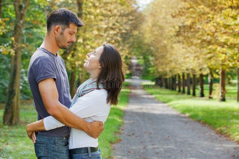 Unga par som går i höstpark royaltyfri bild