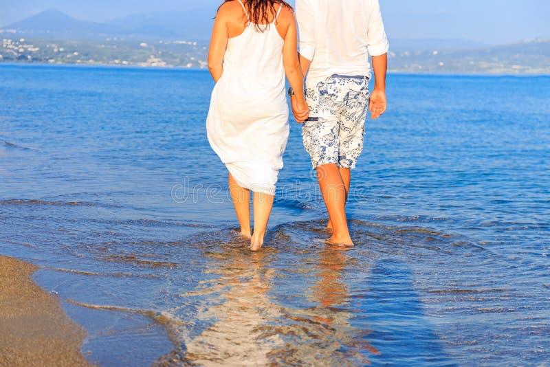 Unga par som går längs ensam strand på solnedgången arkivfoto