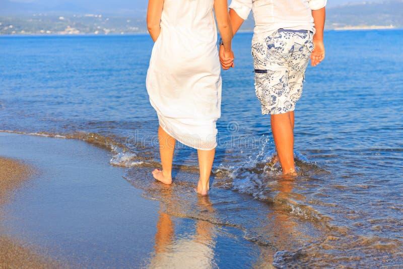 Unga par som går längs ensam strand på solnedgången arkivfoton